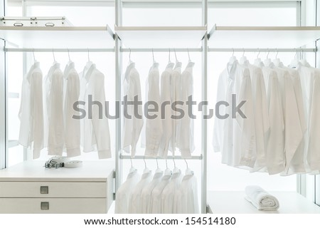 White apparels in built in white wardrobe with racks, drawers, and coat hangers - stock photo