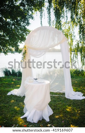 white arch for marriage registration on the background of lake and greenery
