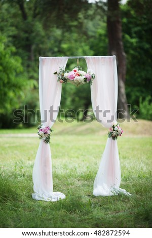 white arch with flowers for outdoor wedding ceremony on the background of green grass and trees in the summer in the Park