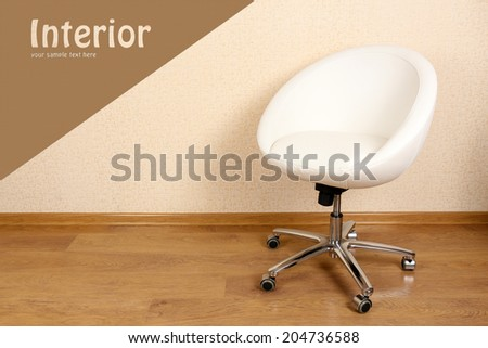 White armchair against wall in room - stock photo