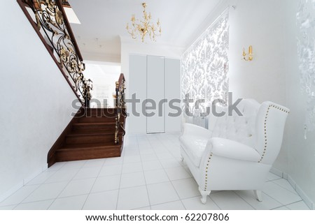 white armchair in the hallway with a staircase