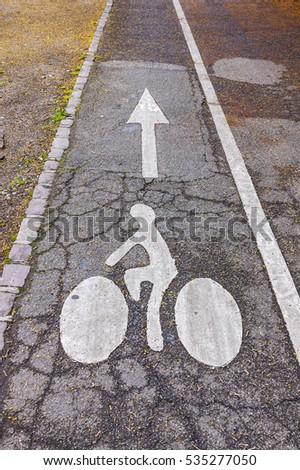 White arrow and bicycle road sign on asphalt