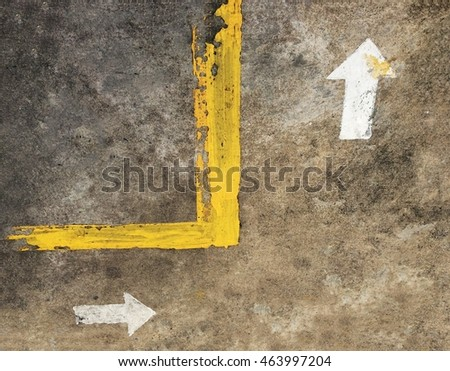 white arrow and yellow line on concrete ground, soft focus and low key