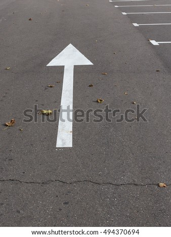 white arrow narisovanna special paint on the gray asphalt cracked and fallen leaves on the road on the street