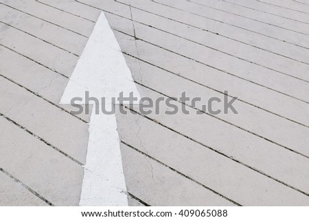 White arrow on concrete road - stock photo