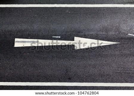 white arrow on the road - stock photo