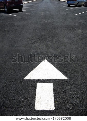 White arrow painted on road for cars to follow directions - stock photo