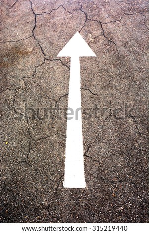 white arrow sign on the dry soil, ground, background