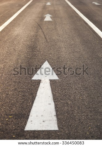 White arrow straight. Is on the road to a straight forward direction.