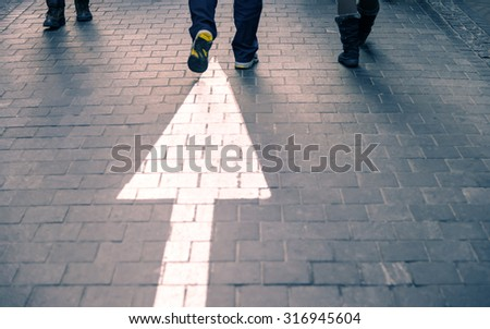 White arrow straight on pavement walking street with walking people - stock photo