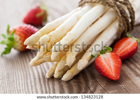 white asparagus and strawberries on wooden table - stock photo