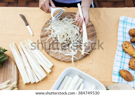 white asparagus on a table, woman is peeling the asparagus, topview