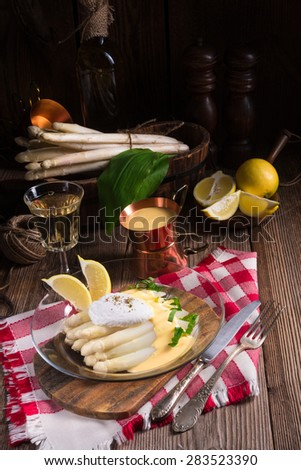 white asparagus served with a fine hollandaise sauce and Poache - stock photo