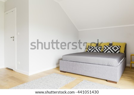 White attic bedroom with double bed and decorative pillows