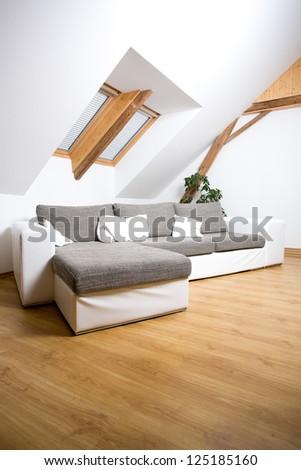 White attic room with a sofa - stock photo