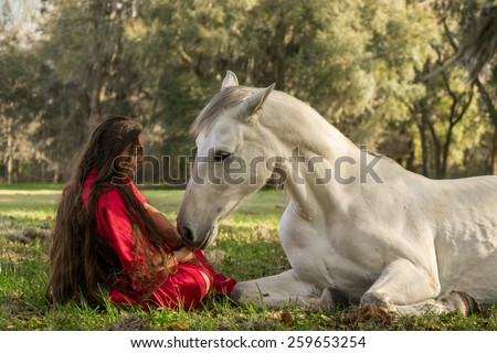 White Azteca horse mare stallion equine lying down in field pasture meadow with young woman girl lady in a red dress gown sitting down looking romantic serene innocent trusting beautiful connected - stock photo