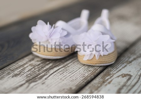 White baby girl shoes on wooden background. - stock photo
