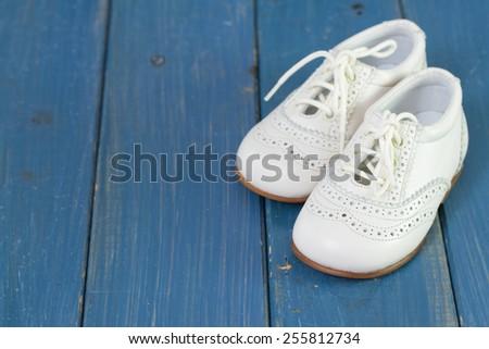 white baby shoes on blue background - stock photo