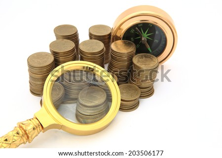 white background heap coins lie, through magnifying glass the compass