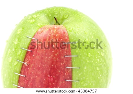 White background studio image of genetically modified objects concept made by different types and colors of apples stapled together. - stock photo