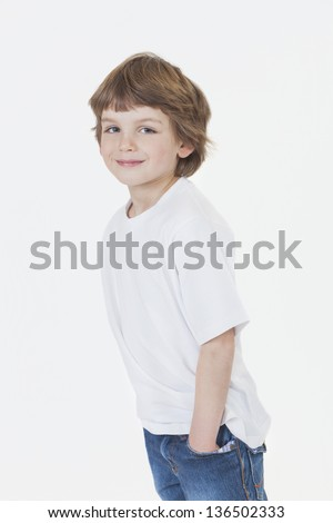 White background studio photograph of young happy boy smiling hands in pockets wearing blue denim jeans and white T-shirt