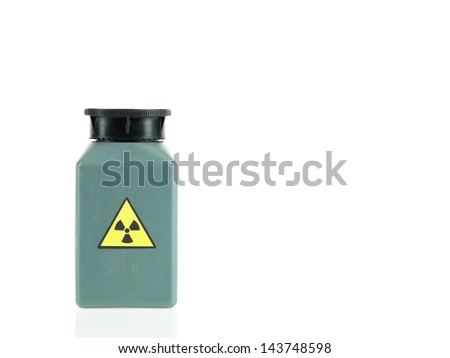 white background with a small green opaque plastic bottle with a black cap and a radioactivity warning label - stock photo