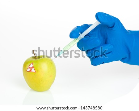 white background with a yellow apple labeled as bio hazardous being injected with a light green transparent substance by a hand in a blue rubber glove - stock photo