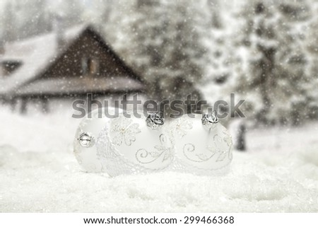 white balls in snow and home in forest background  - stock photo