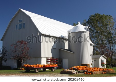white barn and silo with pumpkins