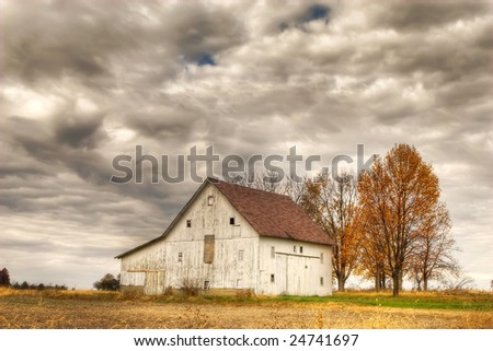 White barn in autumn with storm clouds rolling in - stock photo