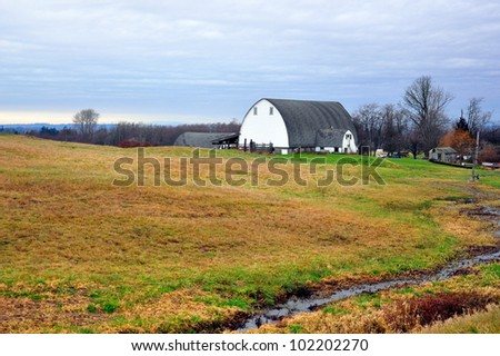 White barn on the horizon with grassy field - stock photo