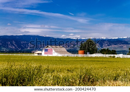 White barn with American flag painted on the side in front of growing wheat field near Rocky Mountains - stock photo