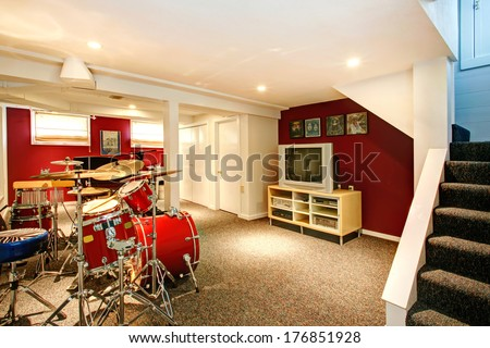 White basement room with red and burgundy walls, carpet floor. Rehearsal room with drums - stock photo