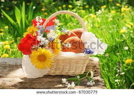 White basket with pasties and flowers on old table in a garden at a summer day