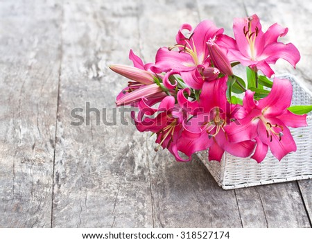 White basket with pink lily flowers bouquet on rustic wooden table - stock photo
