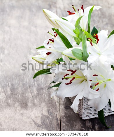 White basket with white lily flowers bouquet on rustic wooden table  - stock photo