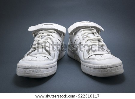 White basketball sneakers on blue background with black vignette.