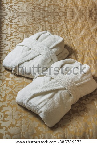 white bathrobe on the bed in the hotel
