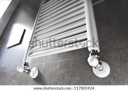 White bathroom heater lighted by the window - stock photo