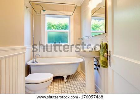 White bathroom with antique white tub, window and tile floor - stock photo
