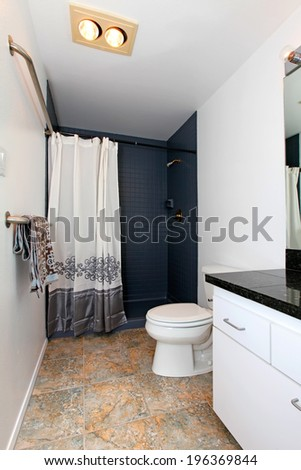 White bathroom with tile floor and tile wall trim. Decorated with towels and curtain