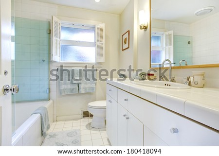 White bathroom with window. White wooden cabinets blend with tile floor and ivory wall