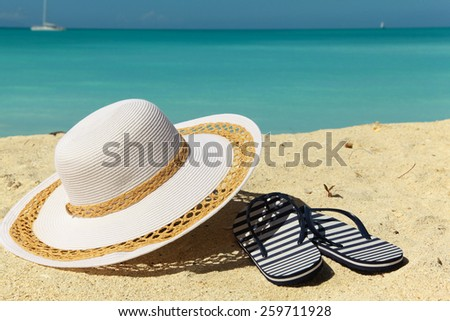 white beach hat and thongs on sand - stock photo