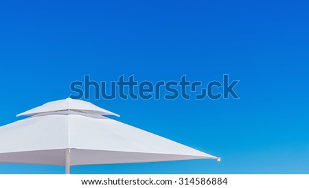 White beach umbrella at the clean blue sky.