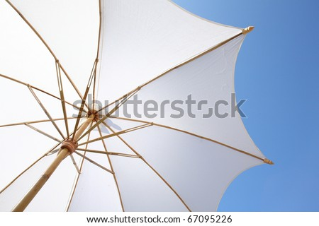 white beach umbrella with blue sky - stock photo
