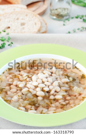 White bean soup with thyme and rosemary, selective focus, vertical - stock photo