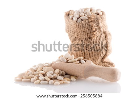 White beans bag with wooden scoop on white background. - stock photo