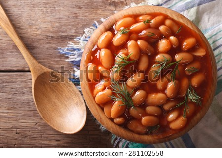 white beans in tomato sauce in a wooden bowl closeup. Horizontal top view - stock photo