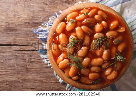 white beans in tomato sauce with dill in a wooden bowl closeup. horizontal view from above - stock photo