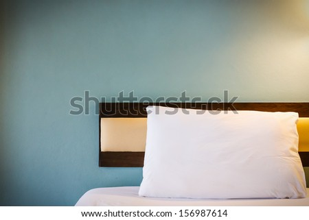 white bed with one pillow, light blue wall - stock photo